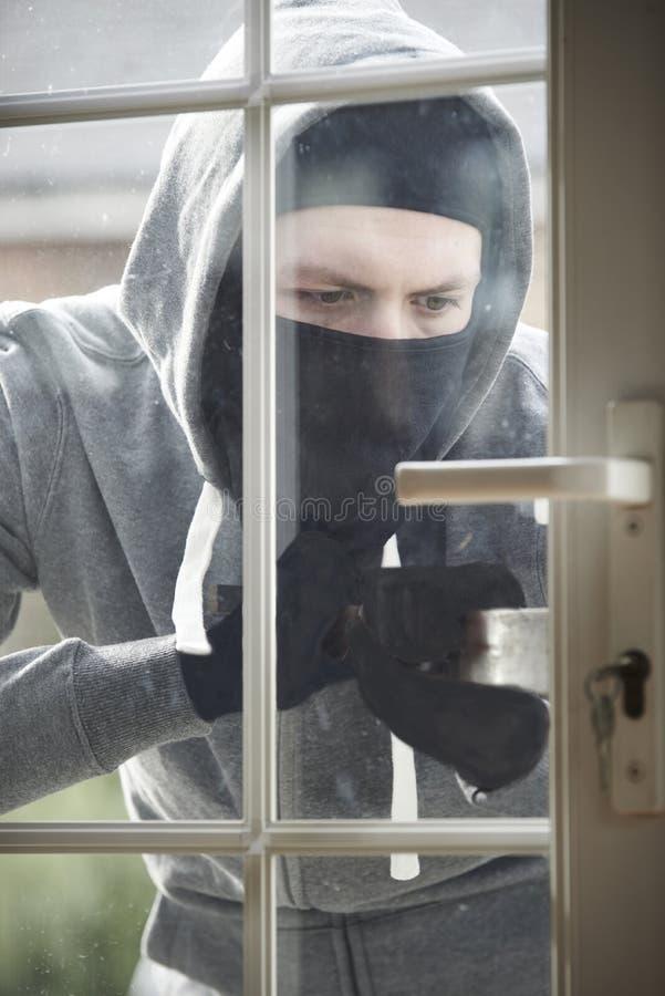 Scassinatore Breaking Into House con la forzatura della porta con il bastone a leva immagini stock