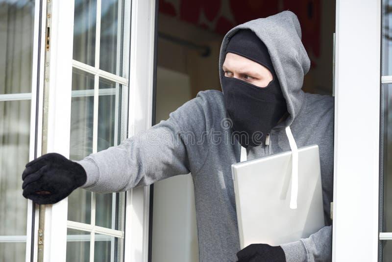 Scassinatore Breaking Into House e computer portatile rubare fotografie stock libere da diritti