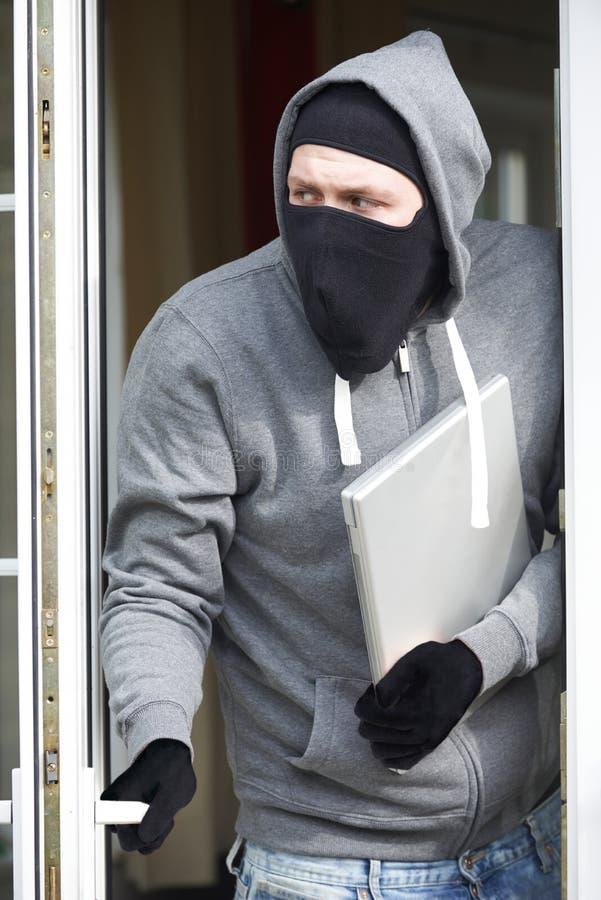 Scassinatore Breaking Into House e computer portatile rubare fotografia stock