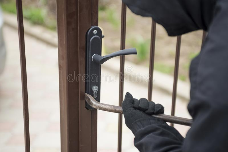 Scassinatore che prova a rompere il portone con un bastone a leva Ladro che rompe serratura per aprire il portone fotografia stock