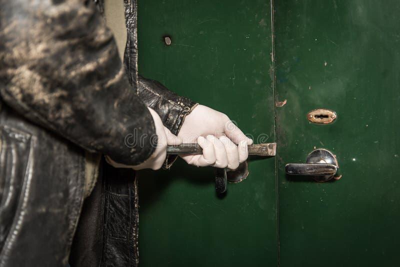 Scassinatore che prova a rompersi in una casa con il bastone a leva fotografia stock