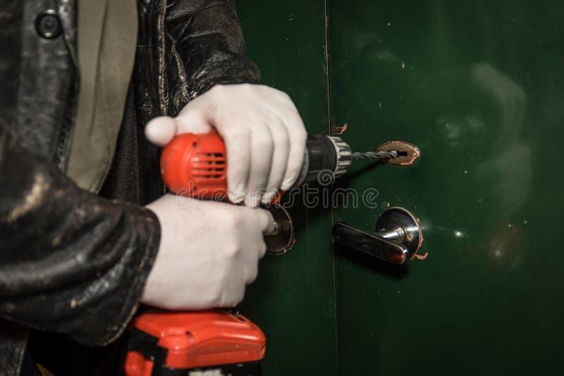 Scassinatore che prova a rompersi in una casa con il trapano fotografia stock
