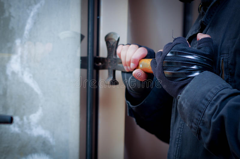 Scassinatore con il bastone a leva per rompere porta per entrare nella casa immagini stock