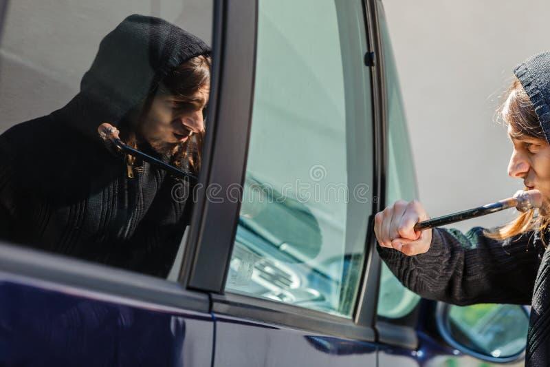 Scassinatore del ladro che si rompe fracassando la finestra di automobile immagini stock libere da diritti