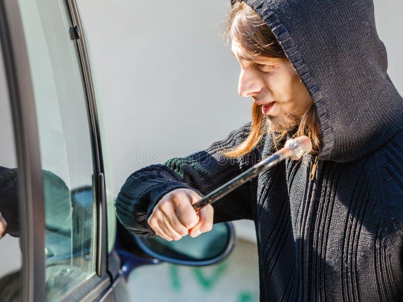 Scassinatore del ladro che si rompe fracassando la finestra di automobile fotografia stock libera da diritti