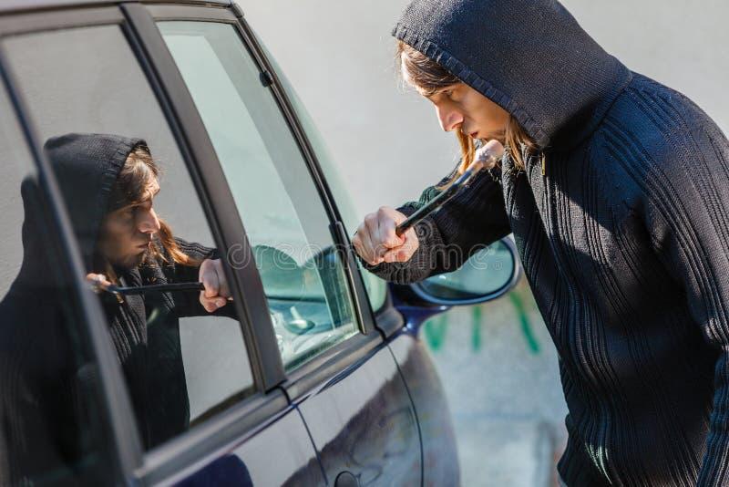 Scassinatore del ladro che si rompe fracassando la finestra di automobile immagini stock