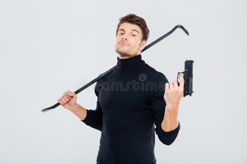Scassinatore sicuro del giovane che posa con la pistola ed il bastone a leva immagine stock