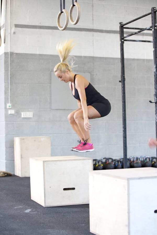 Scatola adatta della giovane donna che salta alla palestra di forma fisica fotografia stock