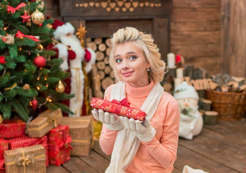 Scatola attuale d'apertura della giovane donna nello studio interno del nuovo anno immagini stock