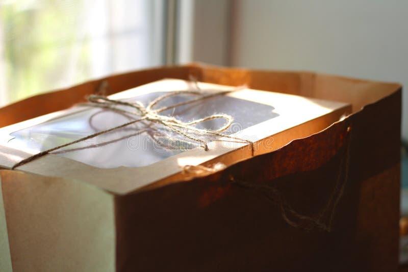 Scatola bianca legata con una corda in un pacchetto del mestiere davanti alla finestra I bigné della bacca sotto il coperchio tra fotografia stock libera da diritti