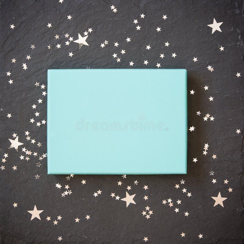 Scatola blu-chiaro rettangolare su fondo nero con le decorazioni d'argento delle stelle Saluti di festa aggancio fotografia stock libera da diritti