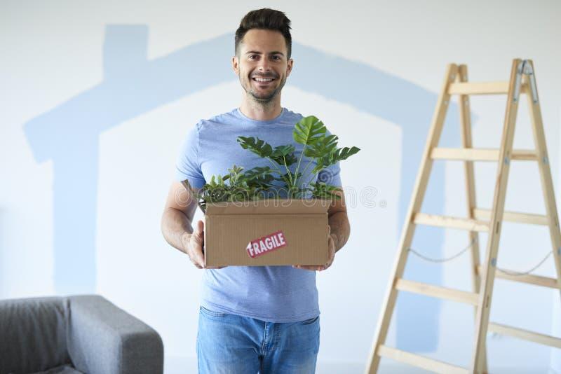Scatola commovente sorridente della tenuta dell'uomo delle piante nella nuova casa fotografia stock libera da diritti