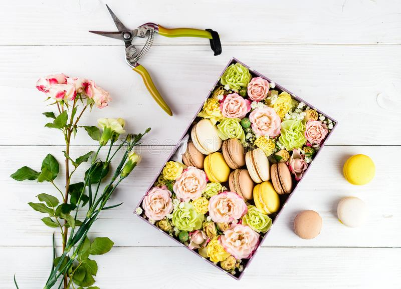 Scatola con i fiori ed i maccheroni, forbici sul backgro di legno leggero fotografia stock libera da diritti