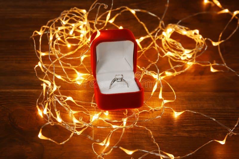 Scatola con l'anello di fidanzamento di lusso e la ghirlanda d'ardore fotografie stock