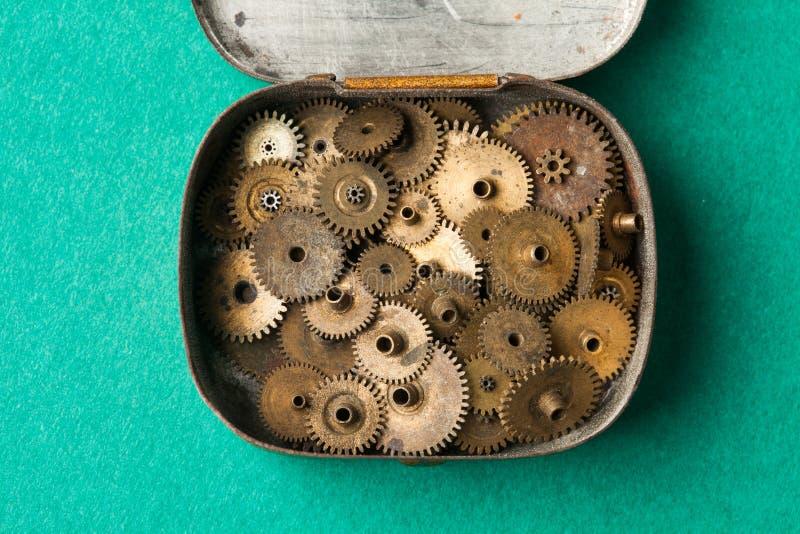 Scatola d'annata aperta con l'insieme invecchiato della raccolta degli ingranaggi di lerciume macro vista, fondo del Libro Verde  immagine stock libera da diritti