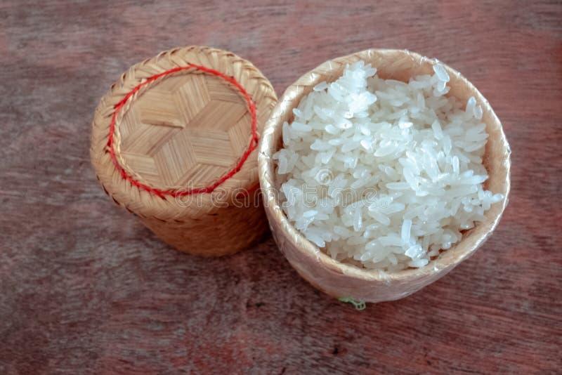 Scatola di bambù di legno di stile tradizionale con riso appiccicoso tailandese su fondo di legno fotografia stock