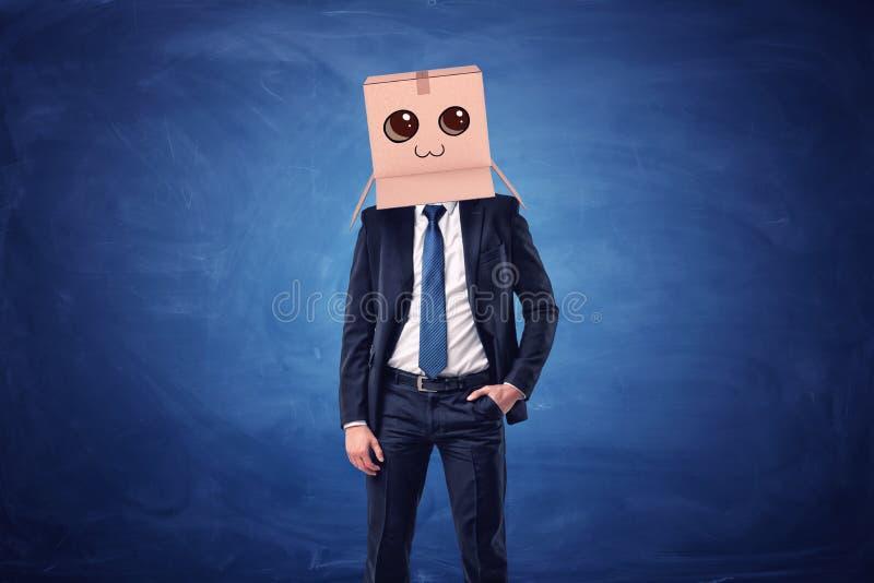 Scatola di cartone d'uso dell'uomo d'affari con il fronte sorridente tirato sulla sua testa su fondo blu immagine stock