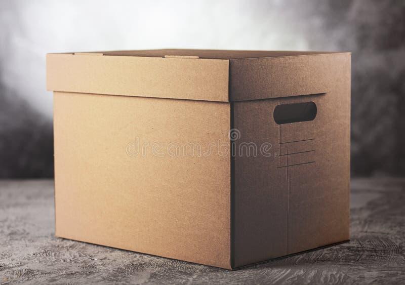 Scatola di cartone su fondo grigio fotografia stock