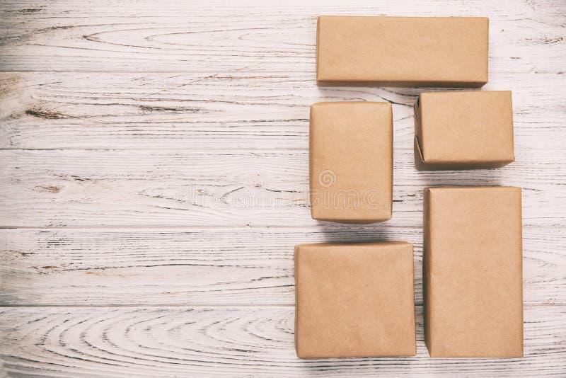 Scatola di cartone su fondo di legno bianco, annata, vista superiore tonificata del pacchetto della posta di Brown immagine stock libera da diritti