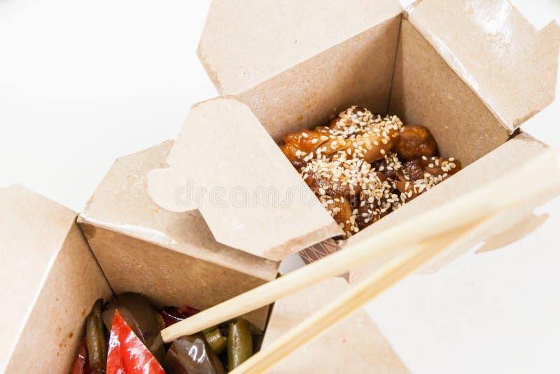 Scatola di consegna con alimento cinese - pollo in glassa agrodolce con sesamo immagini stock