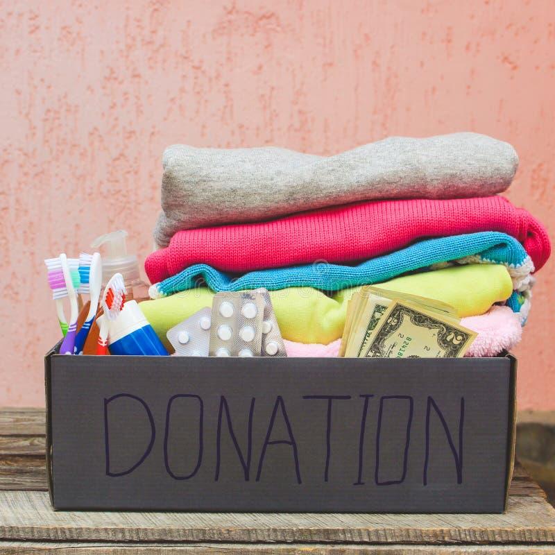 Scatola di donazione con i vestiti, gli elementi essenziali viventi ed i soldi fotografia stock libera da diritti
