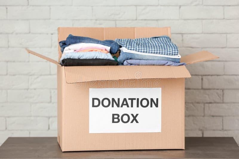 Scatola di donazione con i vestiti sulla tavola fotografia stock libera da diritti