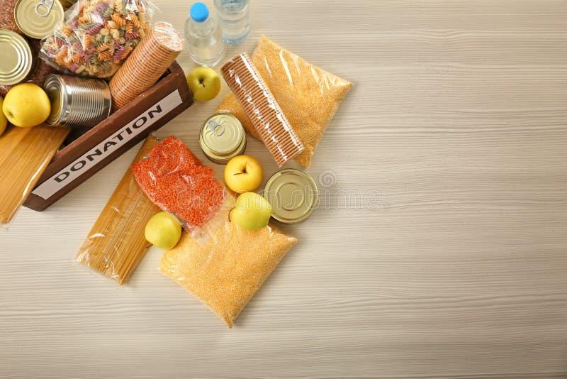 Scatola di donazione e prodotti differenti sulla tavola di legno, vista superiore immagine stock libera da diritti