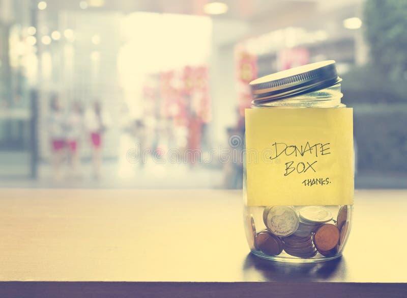 Scatola di donazione, moneta nella bottiglia di vetro, tono d'annata di colore fotografia stock libera da diritti