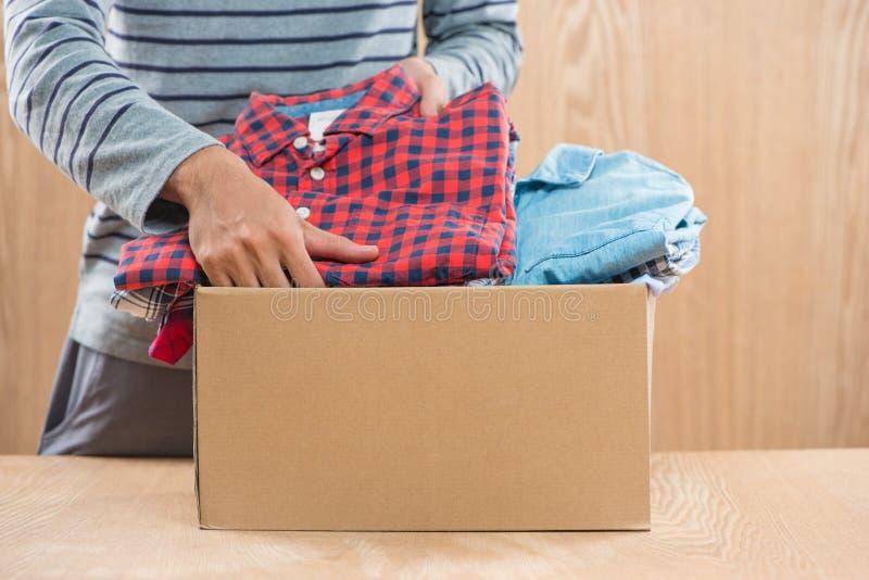 Scatola di donazione per povero con abbigliamento in mani maschii immagini stock