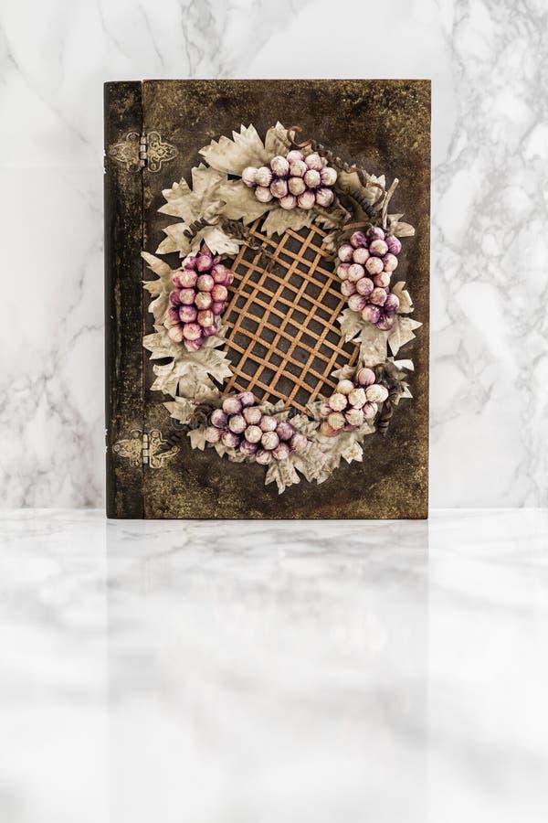 Scatola di legno con l'uva e le figure delle foglie immagine stock
