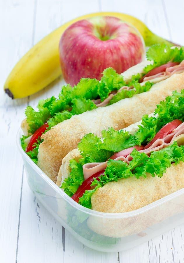 Scatola di pranzo con i panini del pane di ciabatta, mela, banana fotografia stock libera da diritti