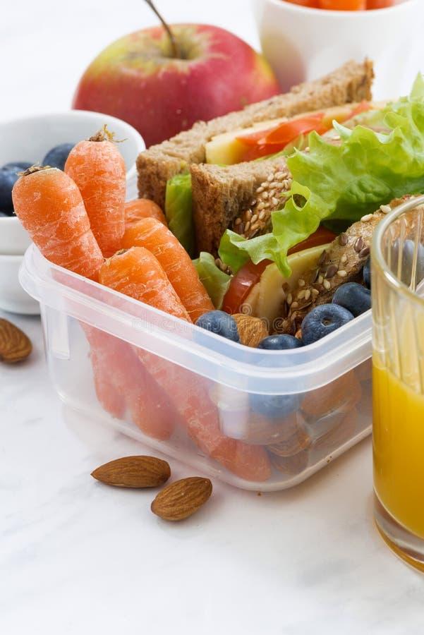 Scatola di pranzo con il panino di pane integrale sulla tavola bianca fotografia stock libera da diritti