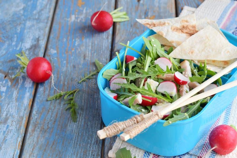 Scatola di pranzo con insalata degli ortaggi freschi - rucola, ravanello, feta, prosciutto e sesamo con la tortiglia piana del pa fotografia stock libera da diritti