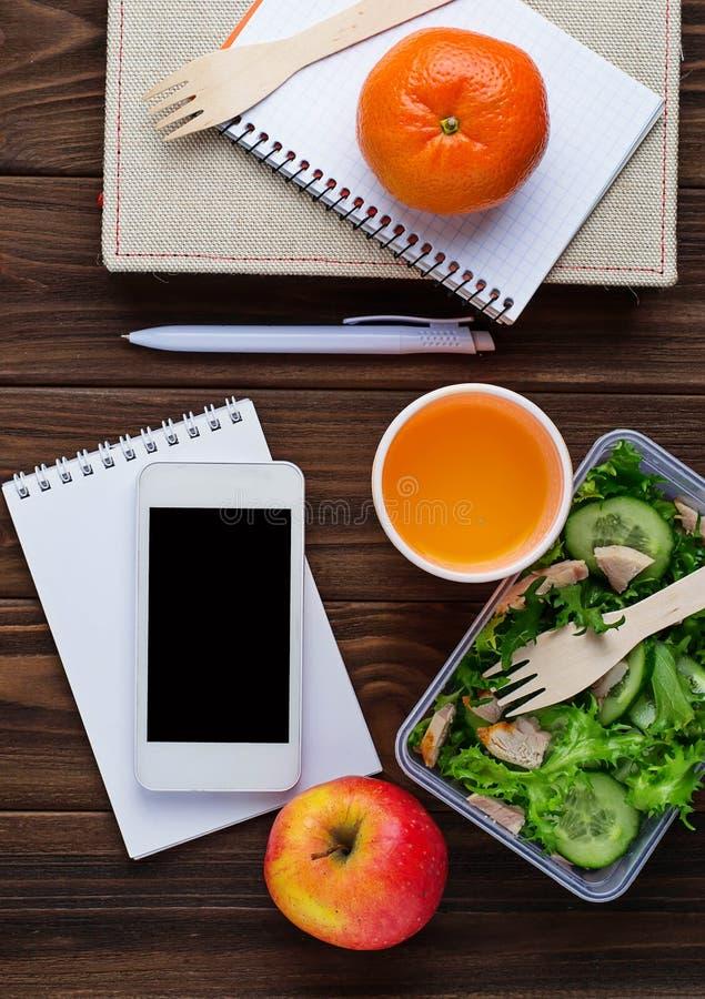 Scatola di pranzo con insalata, il taccuino ed il telefono immagine stock