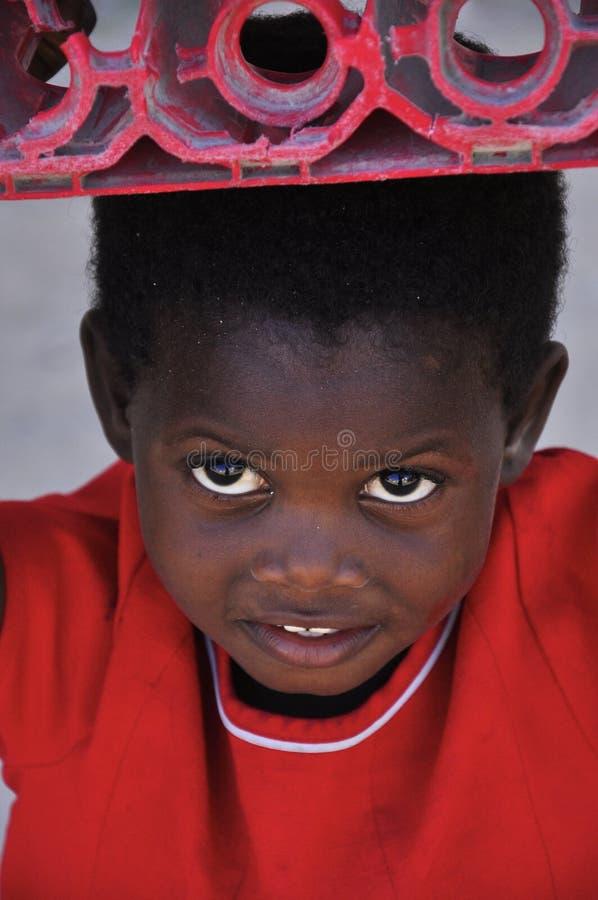 Scatola di trasporto della piccola ragazza sveglia africana sulla sua testa immagini stock libere da diritti