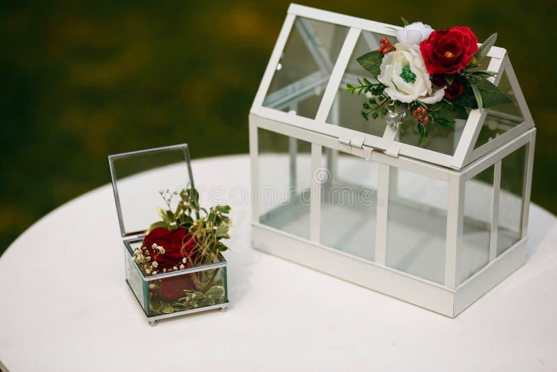 Scatola di vetro alla moda per le fedi nuziali, cerimonia alla moda per le persone appena sposate, accessori decorati con i fiori fotografia stock libera da diritti