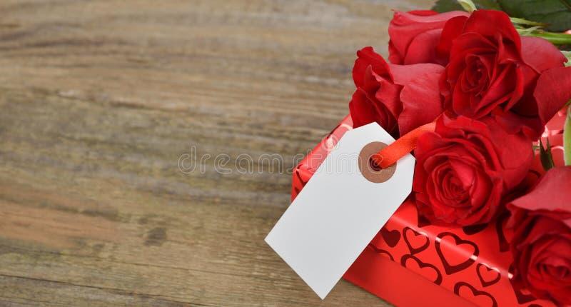 Scatola e rose rosse fotografia stock