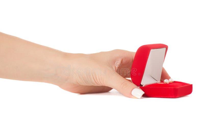 Scatola femminile della tenuta della mano per gli orecchini dei gioielli rossi fotografie stock libere da diritti
