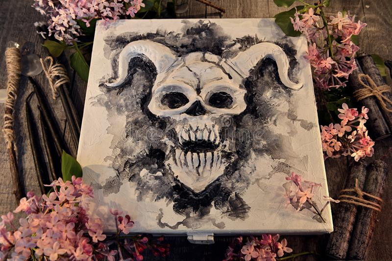 Scatola magica con il fronte del demone o del diavolo, le candele nere ed i fiori lilla immagine stock libera da diritti