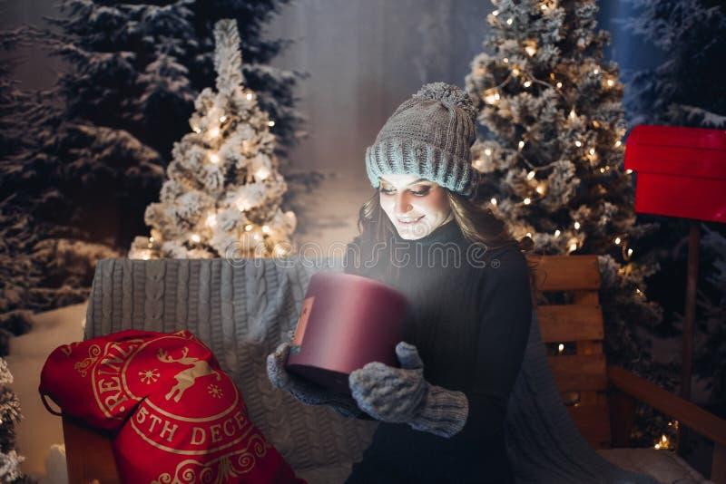 Scatola magica di bella apertura della ragazza con il presente alla notte di Natale immagine stock libera da diritti