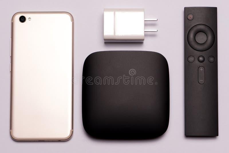 Scatola nera di multimedia TV, regolatore a distanza, Smart Phone e caricatore fotografie stock libere da diritti