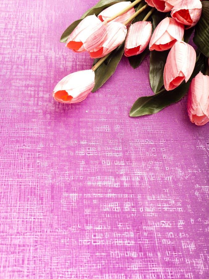 Scatola porpora di regalo e del tulipano su fondo porpora fotografie stock