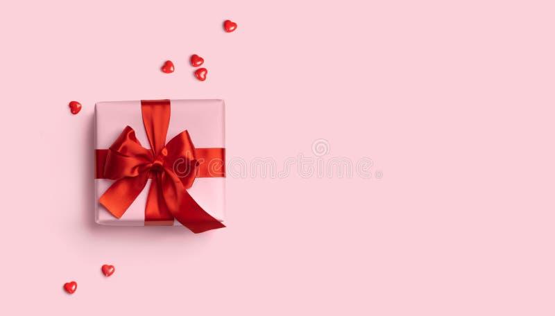 Scatola regalo rosa con arco rosso sullo sfondo rosa con cuori rossi intorno Banner web vacanze Vista dall'alto Piastra piatta Co immagini stock libere da diritti