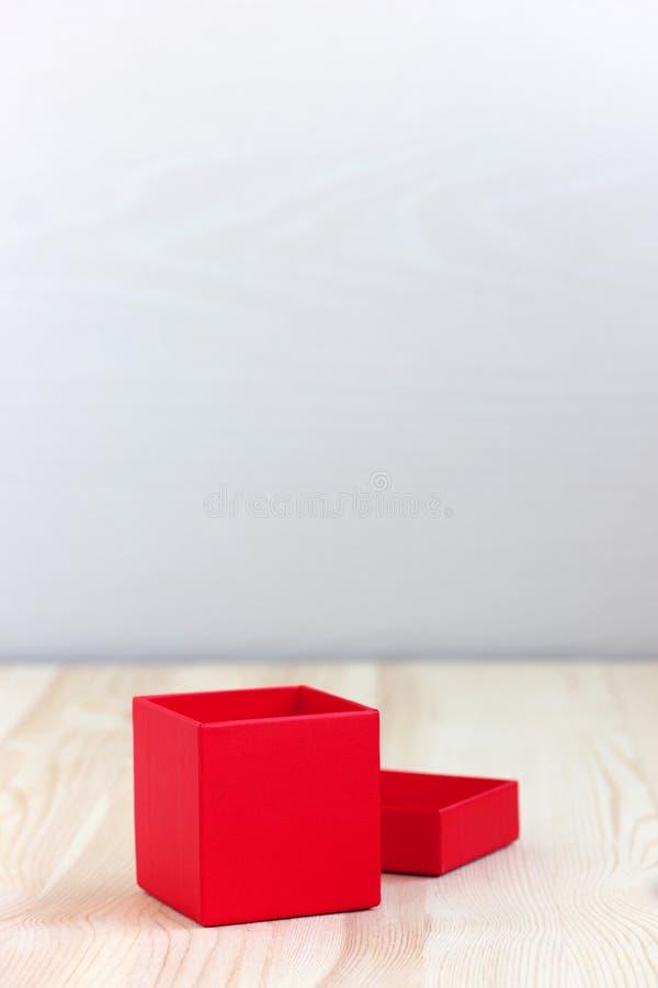 Scatola rossa con il coperchio aperto sulla tavola di legno, fuoco selettivo fotografia stock