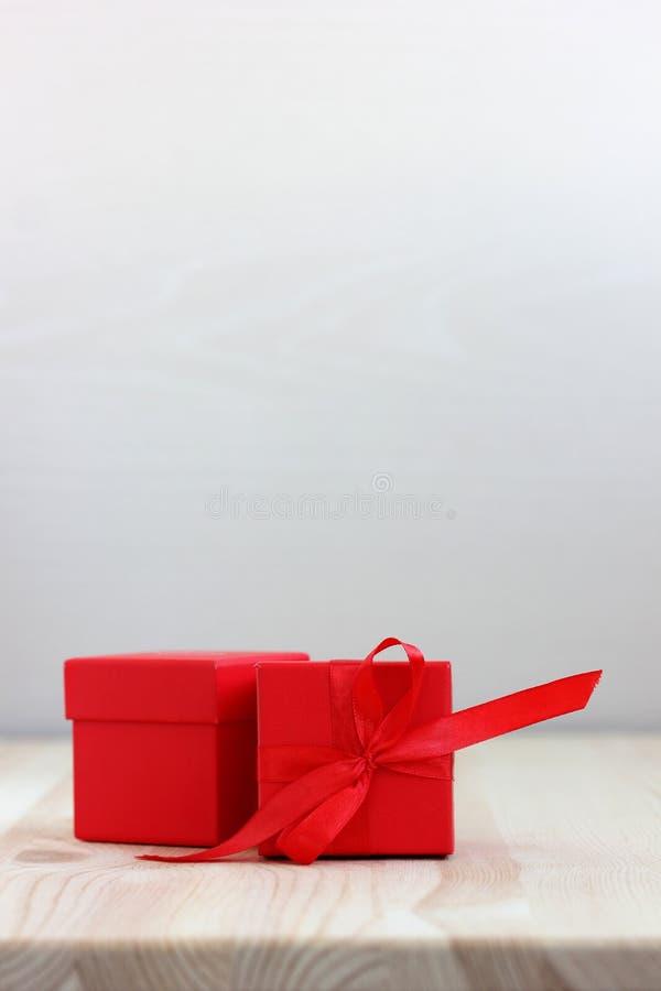 Scatola rossa con l'arco del nastro sulla tavola di legno, fuoco selettivo Spazio per il vostro testo fotografia stock