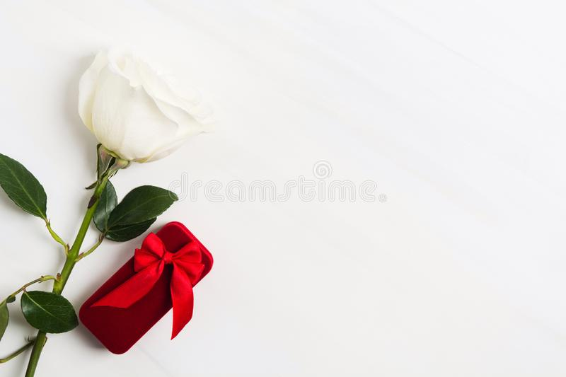 Scatola rossa per gioielli con l'arco rosso e la rosa bianca su fondo strutturato bianco Giorno del ` s del biglietto di S. Valen fotografia stock libera da diritti