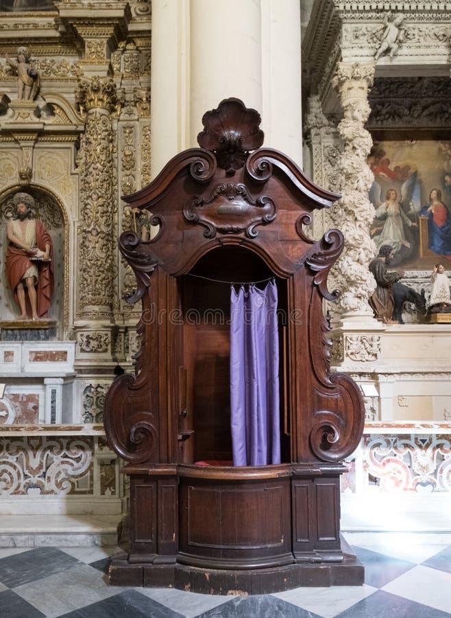 Scatola vuota di confessione con la tenda porpora in una chiesa cattolica in Italia immagine stock
