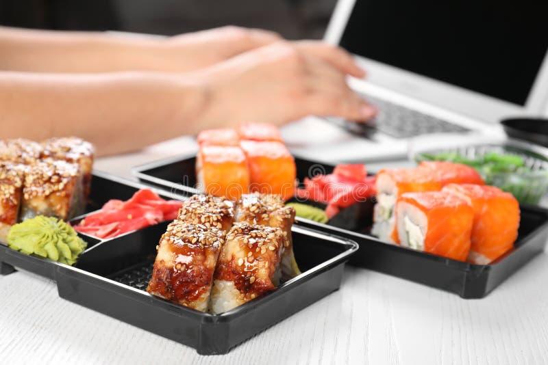 Scatole con differenti rotoli di sushi e donna vaga che per mezzo del computer portatile su fondo immagini stock