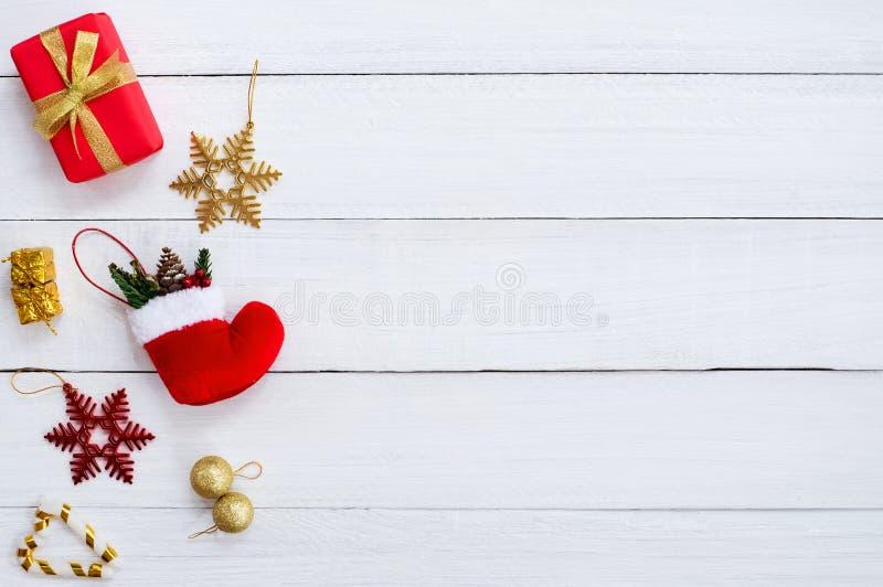 Scatole del GIF di Natale, fiocco della neve, calzino rosso, palla di natale e bastoncino di zucchero sul bordo di legno bianco fotografia stock libera da diritti