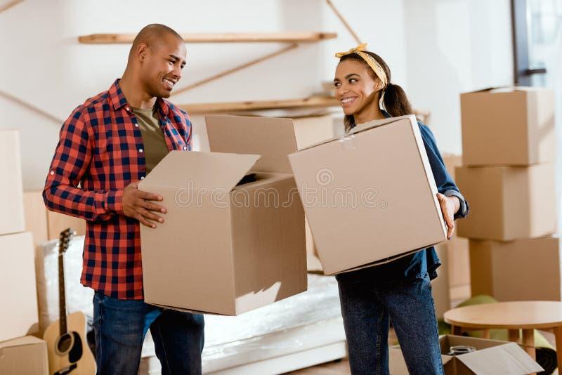 scatole di cartone afroamericane sorridenti della tenuta delle coppie e muoversi verso fotografia stock